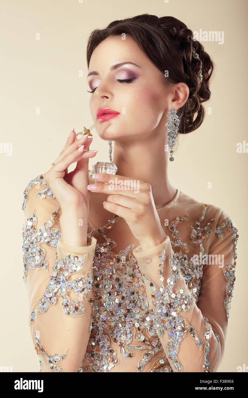 Young Brunette with Perfume Bottle. Fragrance - Stock Image