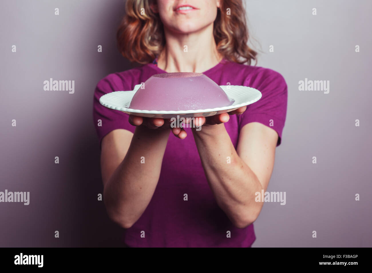 A young woman in a purple top is presenting a plate of jelly - Stock Image