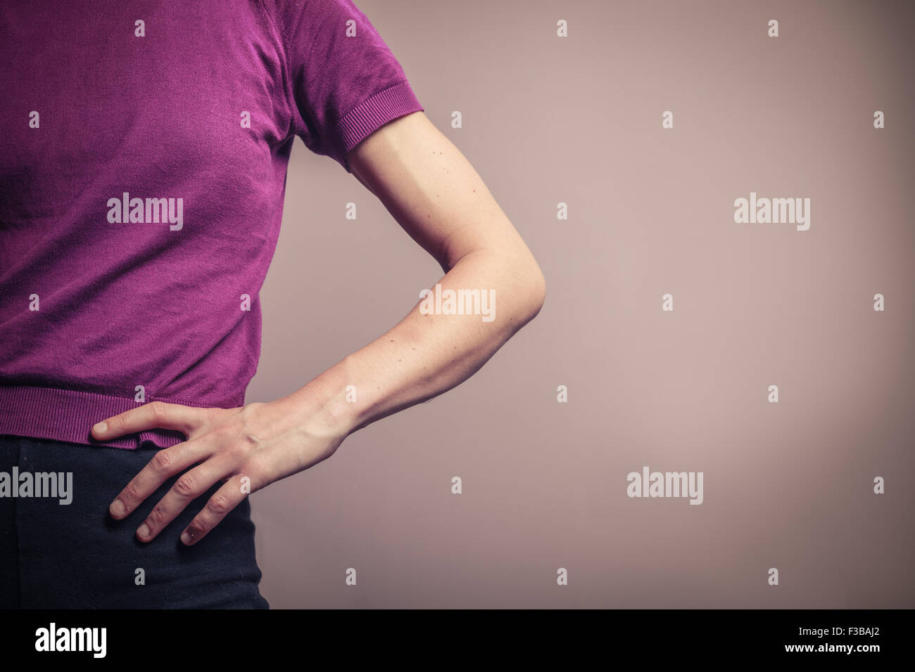 A young woman in a purple top is resting her hand on her hip - Stock Image