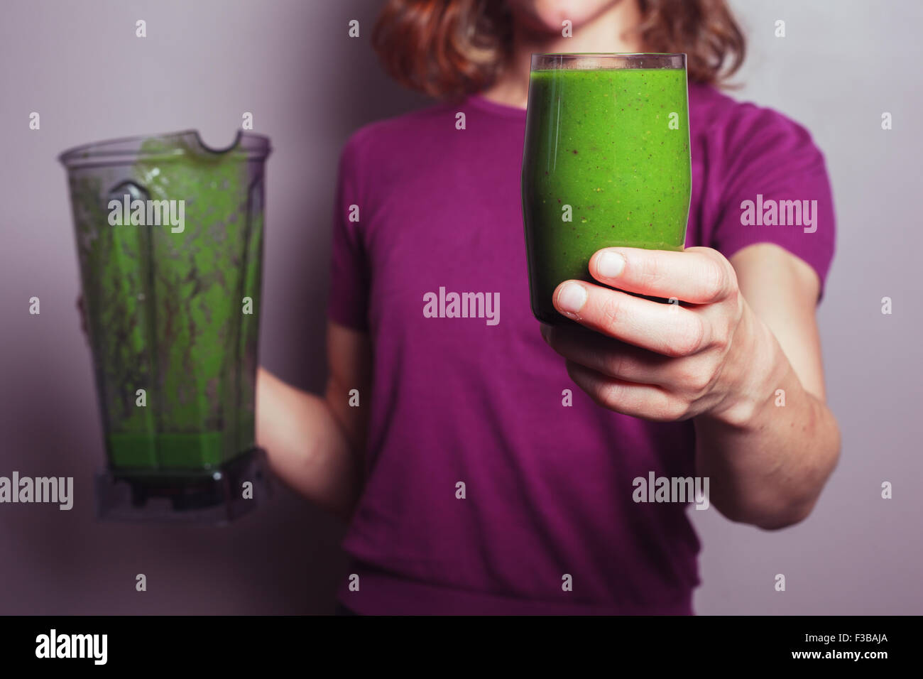 A young woman in a purple top is holding a blender and a glass with green fruit smoothie - Stock Image