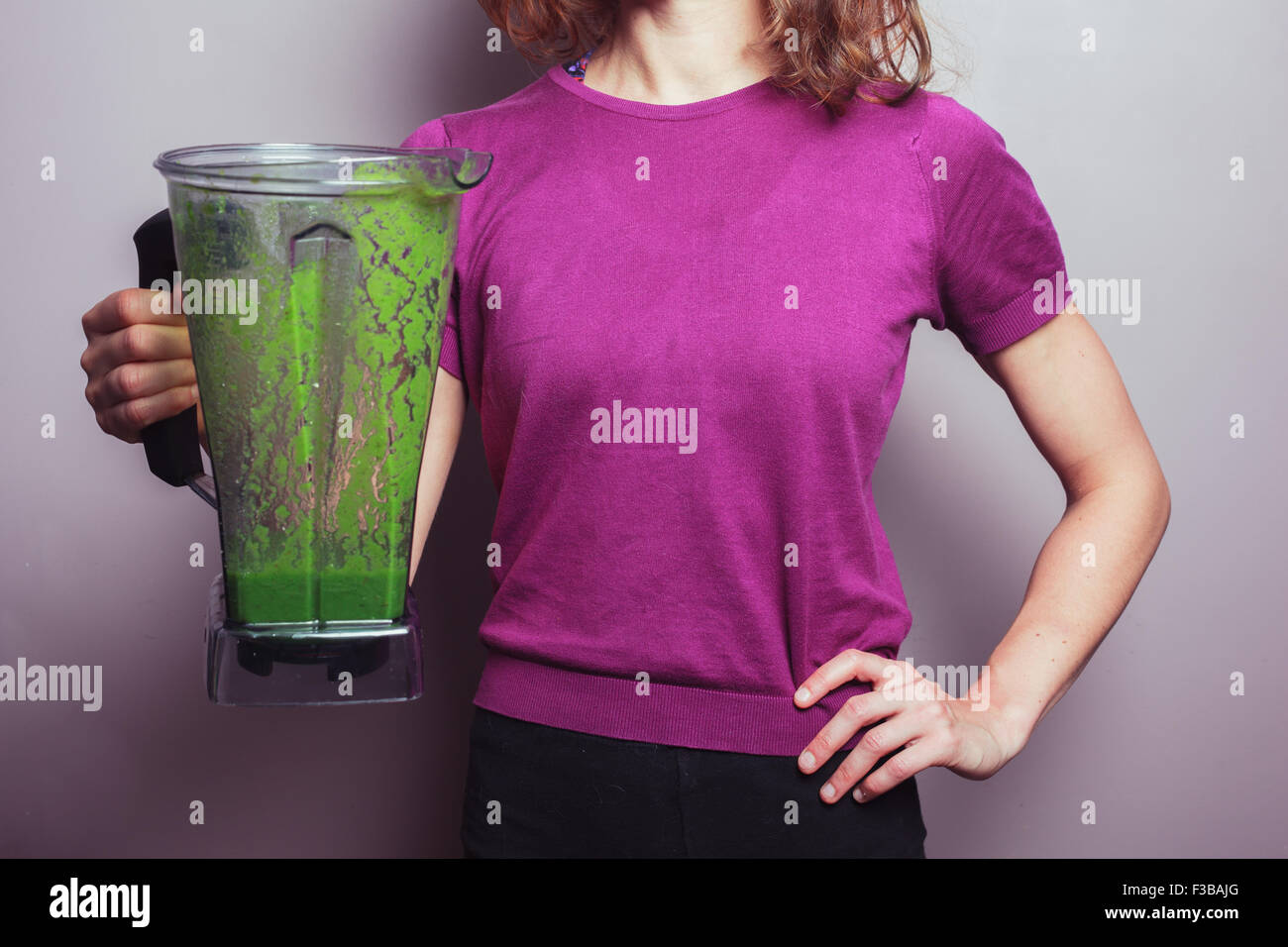 A young woman in a purple top is holding a blender with a green fruit smoothie - Stock Image