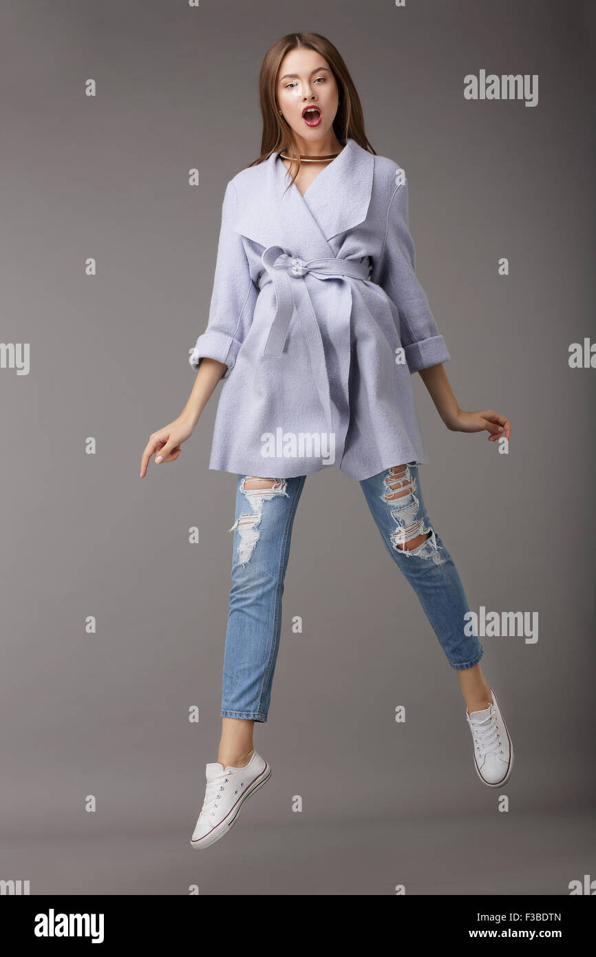 Trendy Young Female Jumping in Blue Coat - Stock Image