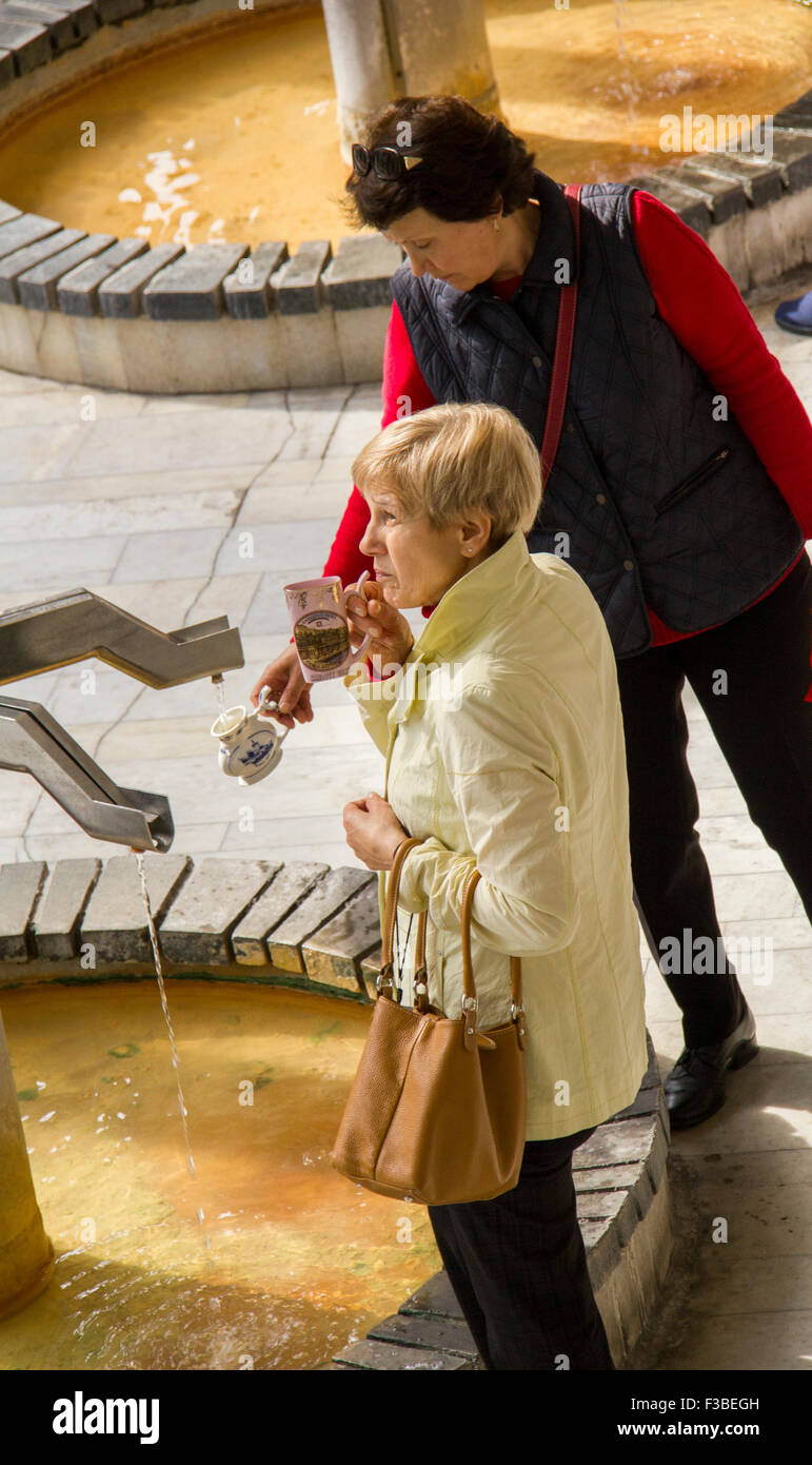 Karlovy Vary, Czech Republic - September 22, 2015: Caucasian woman take water in hottest mineral spring 'Vridlo'. - Stock Image