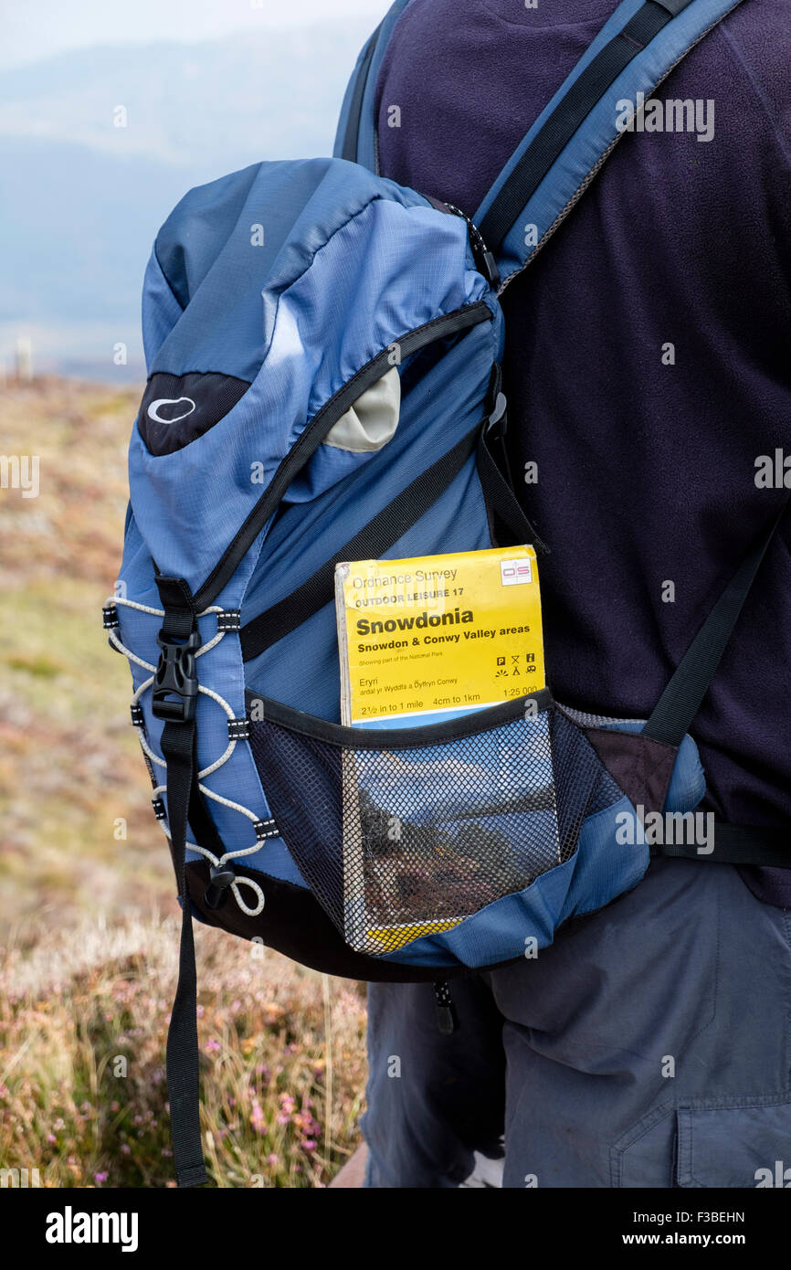 Hiker hiking in mountains of Snowdonia National Park with Ordnance Survey map in a rucksack pocket. North Wales, - Stock Image