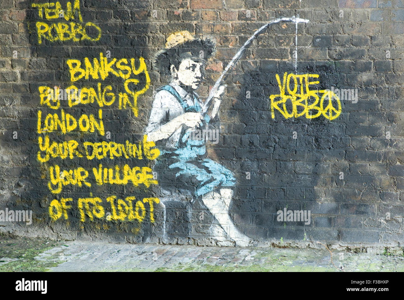 Team Robbo defaces the Banksy image of a little fisher boy on the Regent's Canal in Camden Town in December - Stock Image