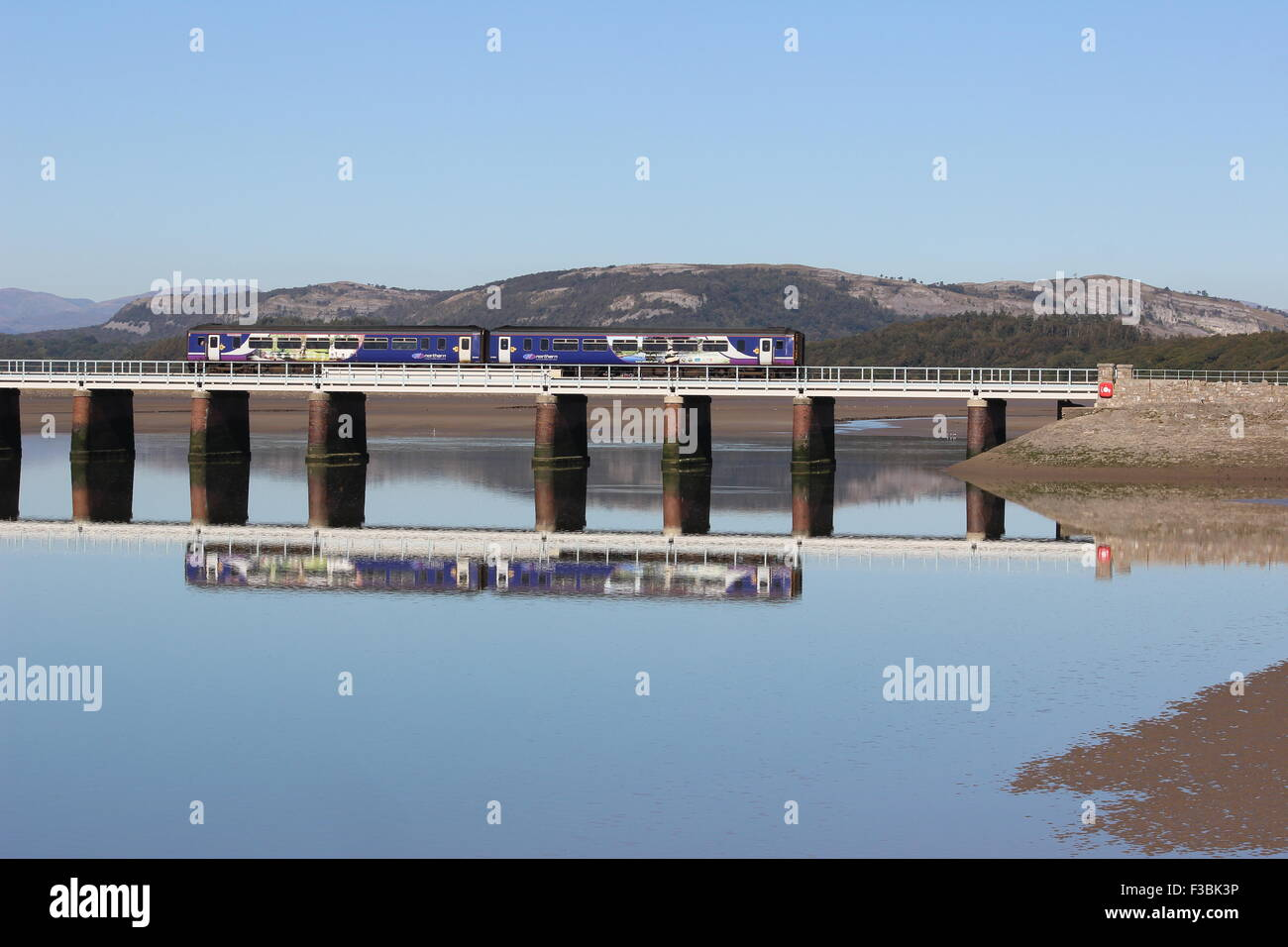 Diesel multiple unit train in Northern livery crossing Arnside Viaduct at high tide with reflection in the River - Stock Image