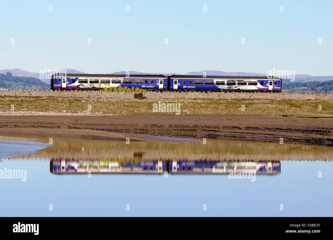 Diesel multiple unit train in Northern livery having just crossed Arnside Viaduct at high tide with reflection in - Stock Image