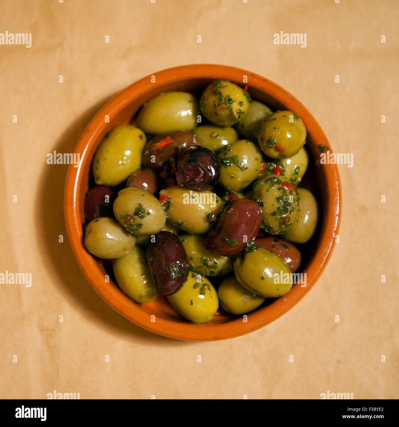 Overhead view of a small bowl of mixed olives - Stock Image