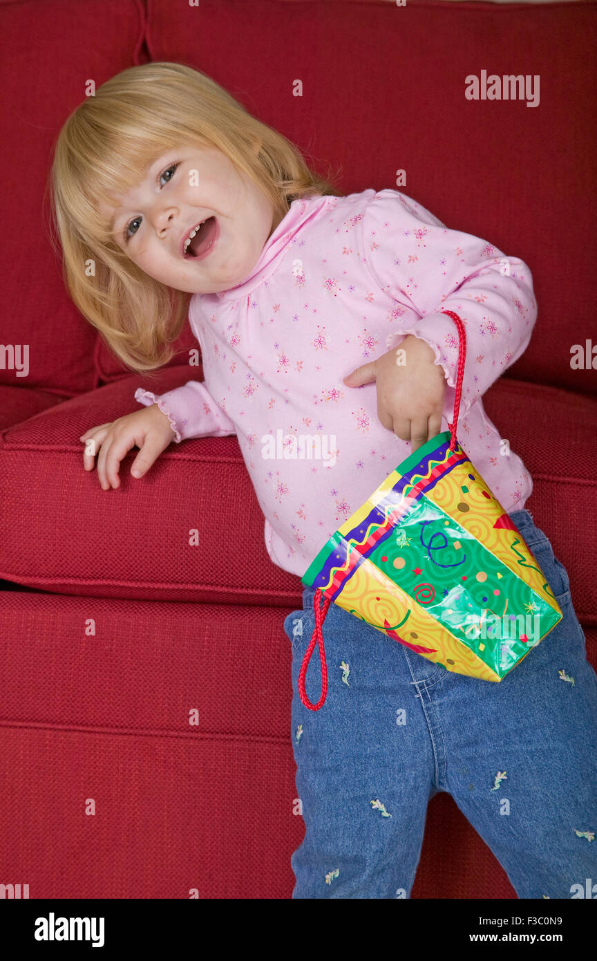 Toddler girl playing with a decorative paper bag, using it as her purse, as she leans on the sofa in Issaquah, Washington, Stock Photo