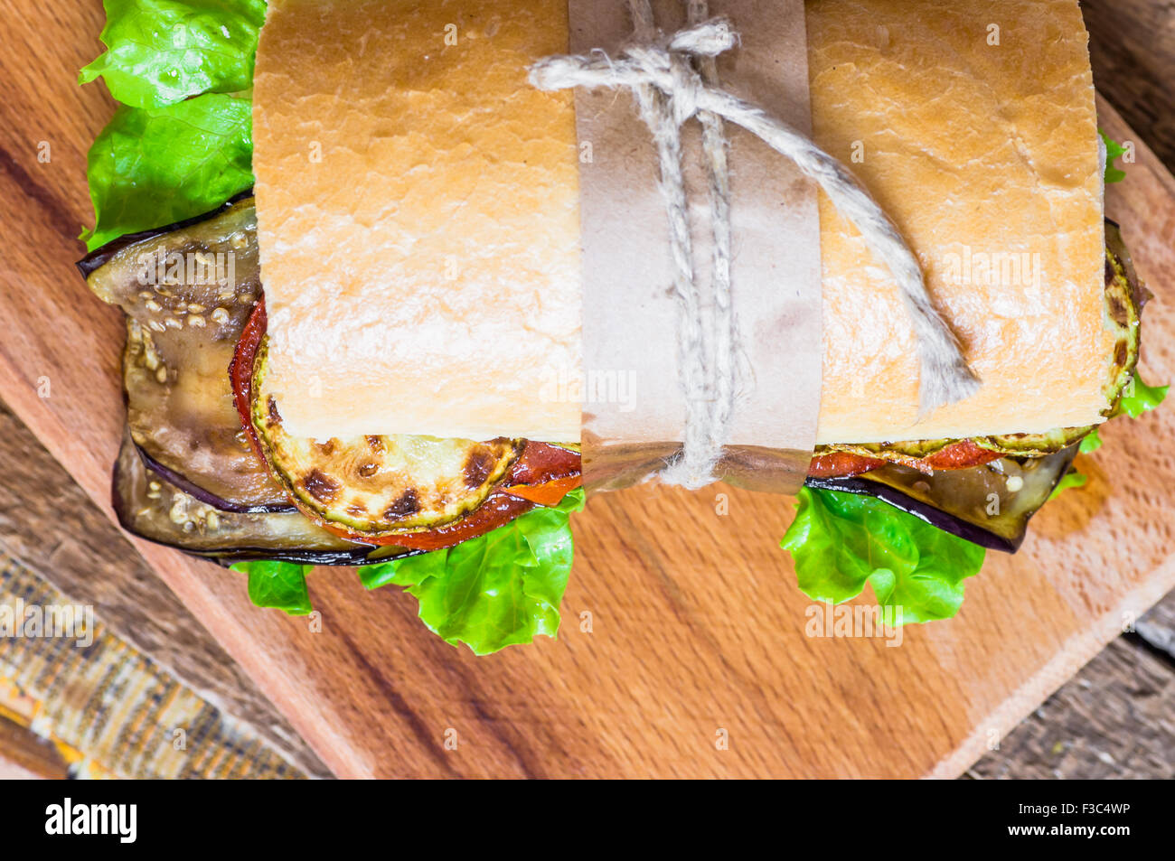 Vegetable vegetarian sandwich with lettuce, zucchini, eggplant and tomato - Stock Image