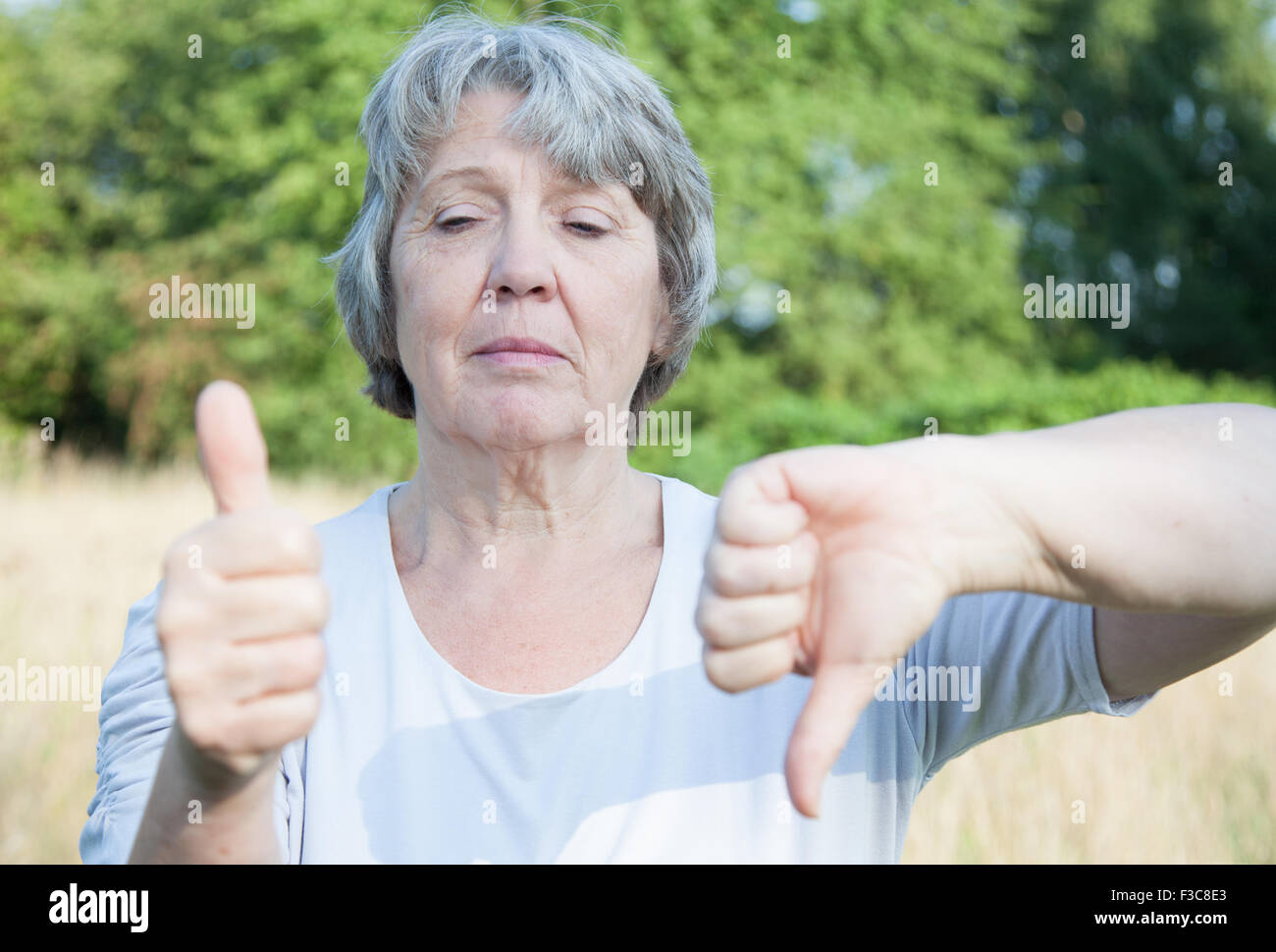 Old age woman showing thumbs up and down - Stock Image