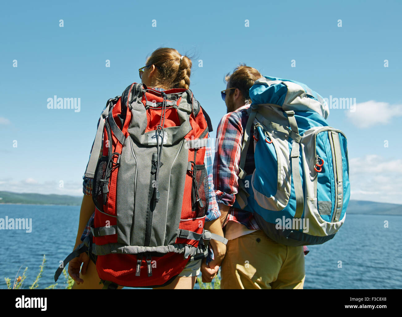 Couple of young hikers with backpacks looking at sea - Stock Image