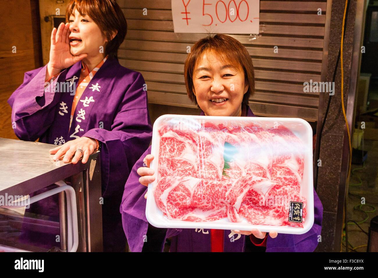Japan, Osaka, Kuromon Ichiba Market, 'Osaka Kitchen', woman seller holding up container of Saga Beef, Sagagyu - Stock Image
