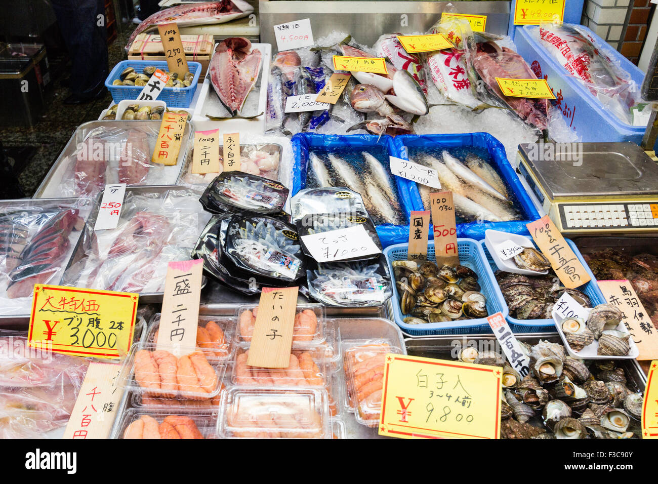 Trays of fishfood on display on stall at Kuromon Ichiba food market in Osaka. Whole fish, prepared fish fillets - Stock Image