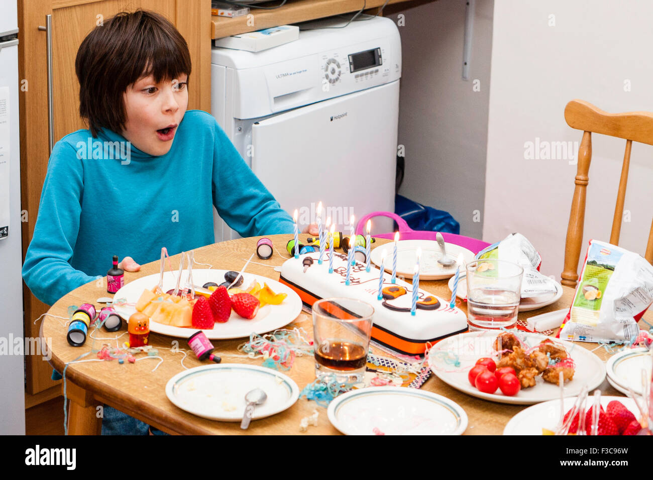 Mixed ethnicity, (Japanese English) 11 year old boy sitting at head of kitchen table blowing candles out on birthday - Stock Image