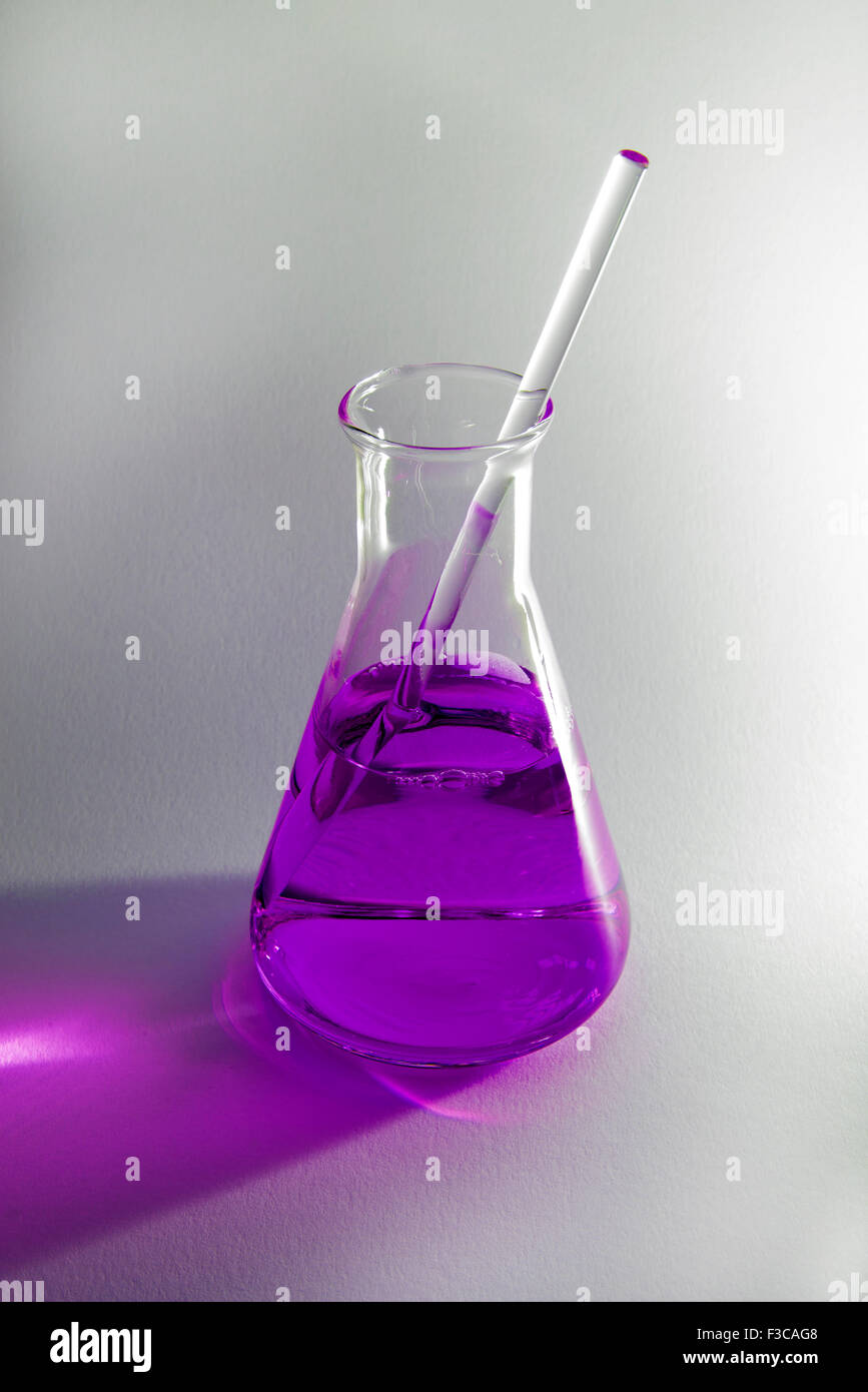 Science flask containing a purple chemical on a plain background - Stock Image