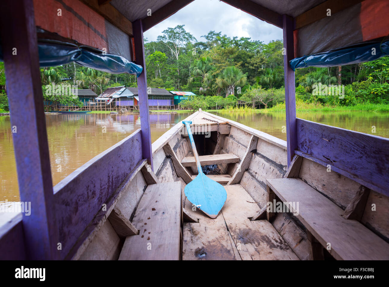 Purple canoe arriving at an island in the Amazon River near Iquitos, Peru - Stock Image