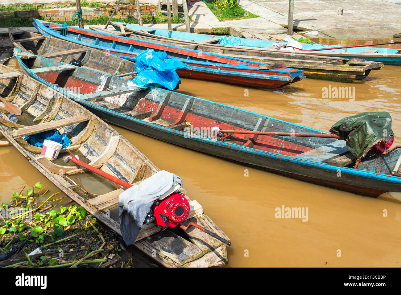 Canoes tied to shore floating on the Amazon River near Iquitos, Peru - Stock Image