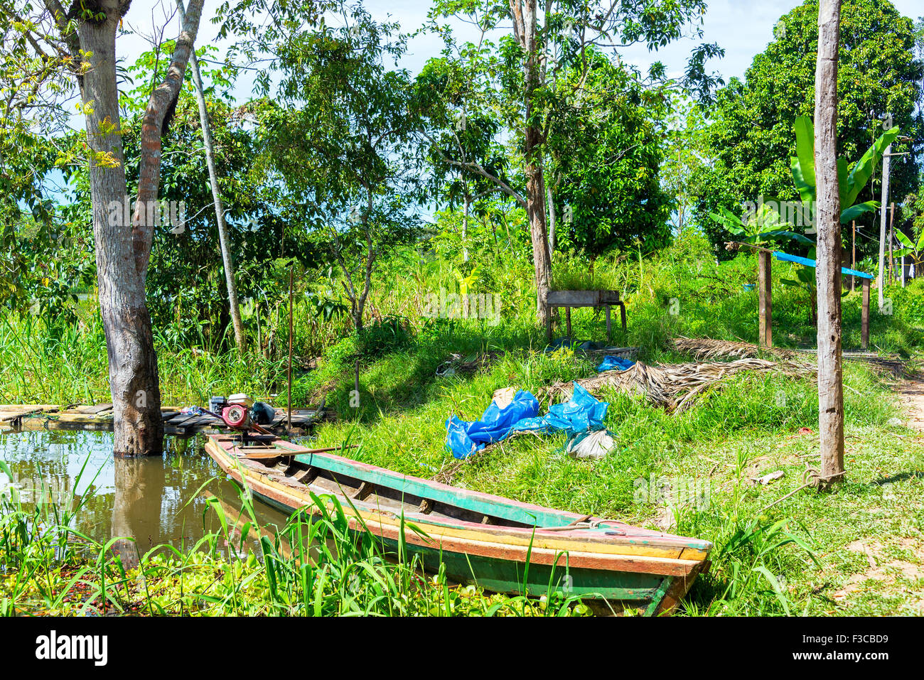 Canoe on the shore of the Yanayacu River in the Amazon rain forest near Iquitos, Peru - Stock Image