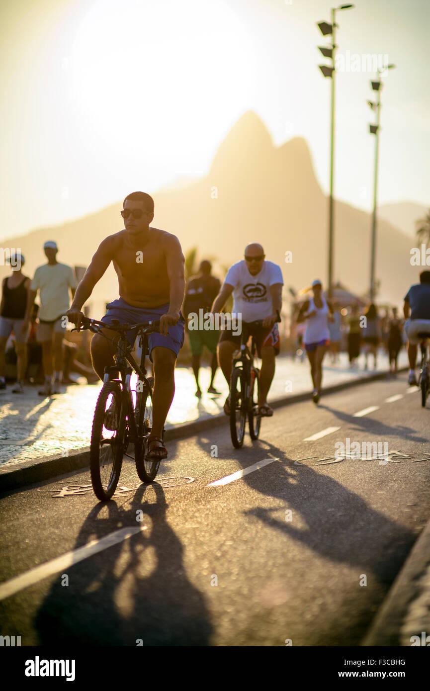 RIO DE JANEIRO, BRAZIL - FEBRUARY 11, 2014: Cyclists and joggers share the bike path alongside pedestrians in Ipanema. - Stock Image