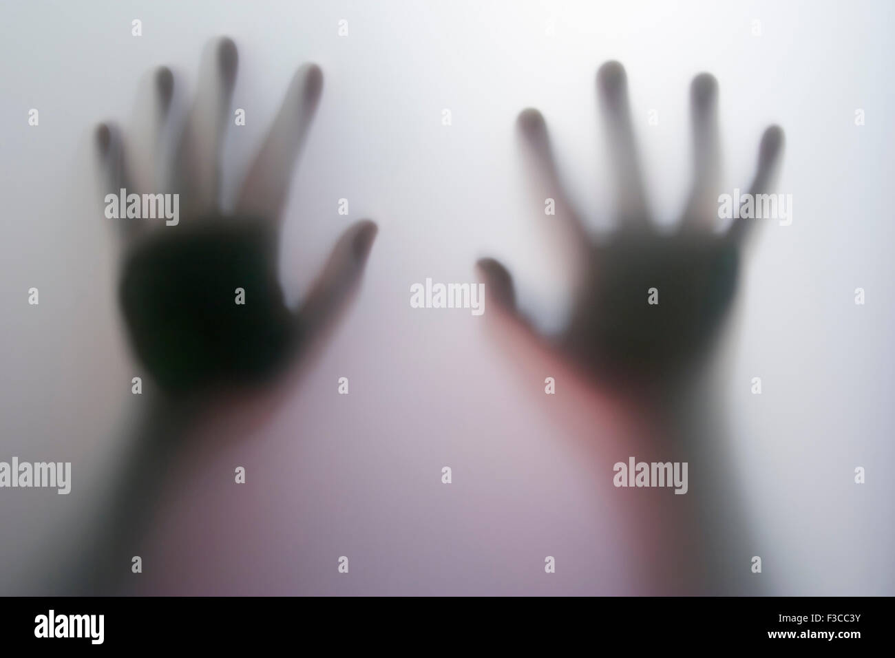 Victim, hands behind glass - Stock Image