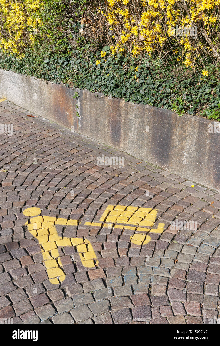 symbol signaling a loading and unloading parking area sign on the pavement of a street in Italy - Stock Image
