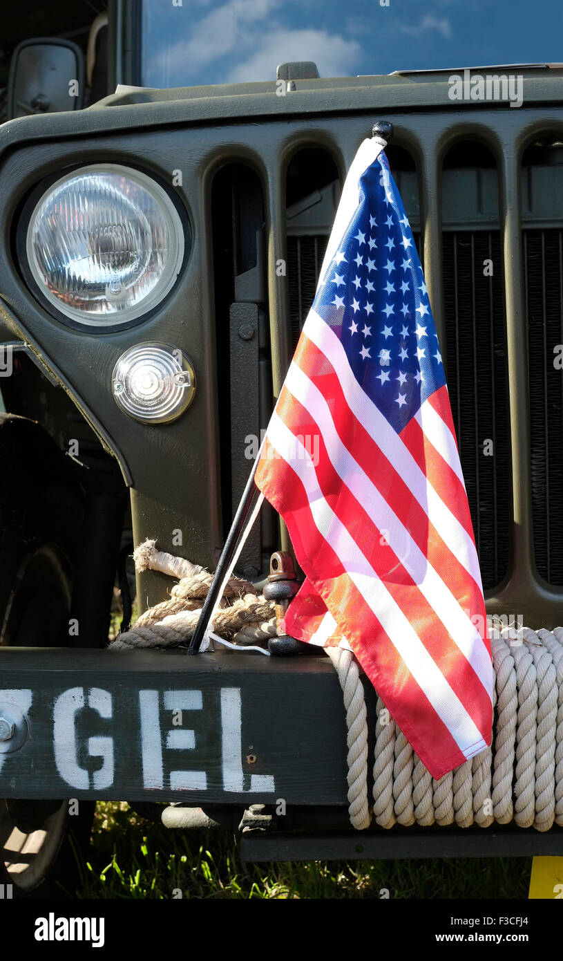 american flag tied to front of old willys jeep - Stock Image