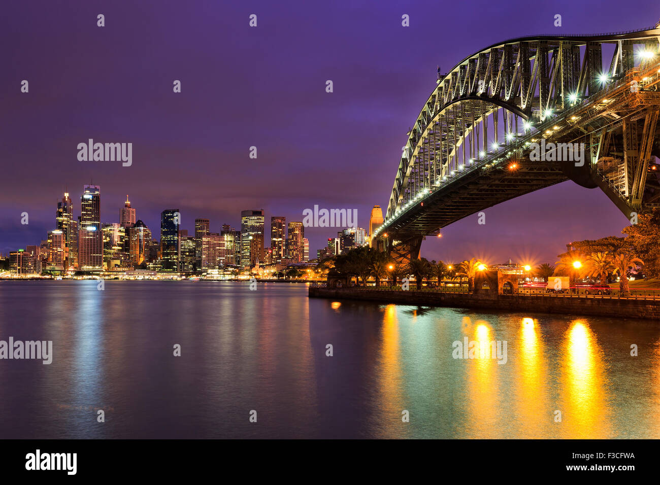 Sydney CBD cityline of illuminated high-rise buildings and harbour bridge with colourful reflection in blurred harbour - Stock Image