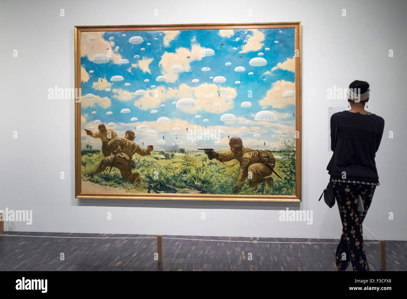 Woman looking at painting  Paratroops Descending on Palembang by Goro Tsuruta at National Museum of  Modern Art - Stock Image