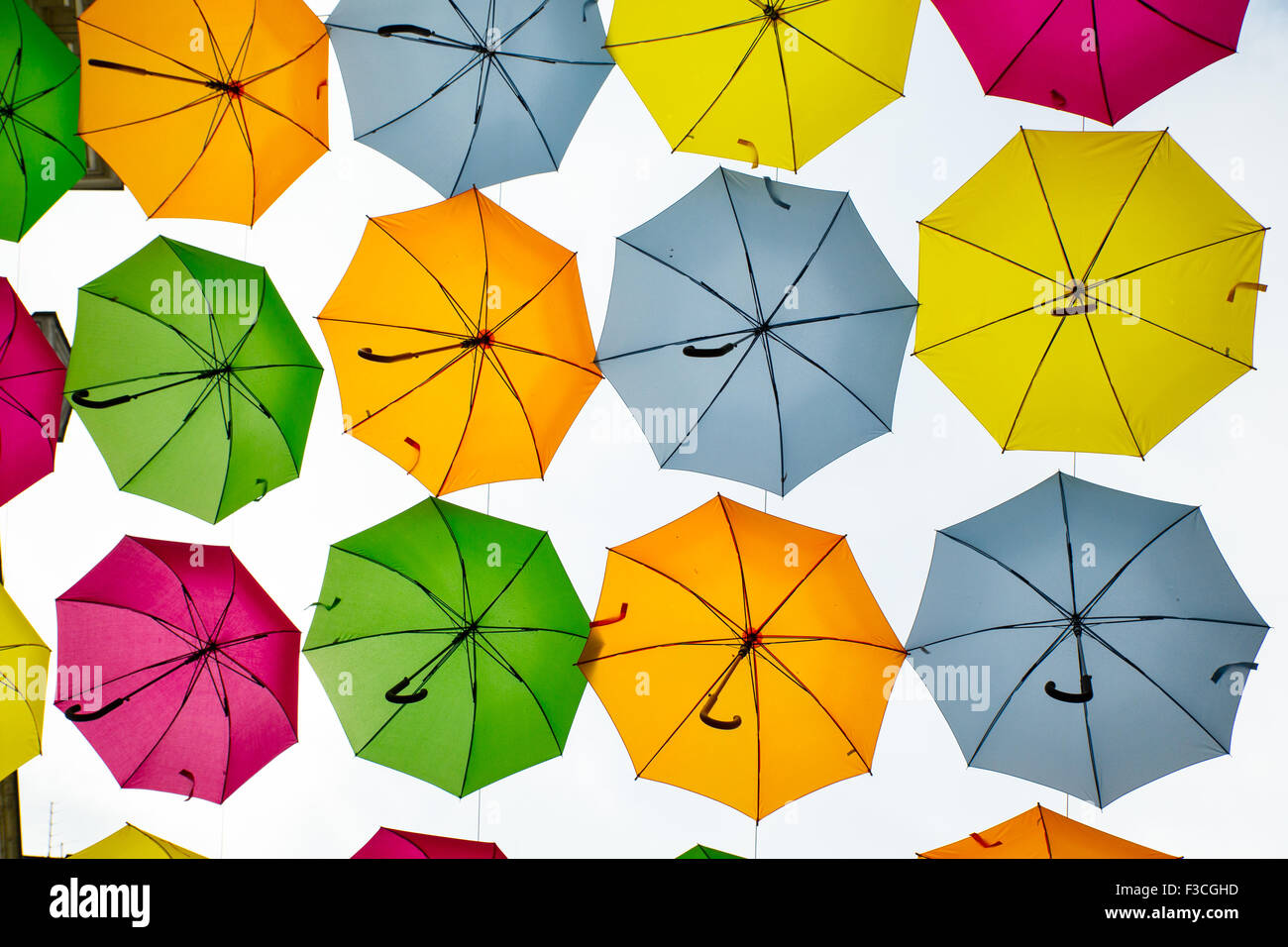 Umbrellas forming a canopy above a street in Saumur, France. - Stock Image