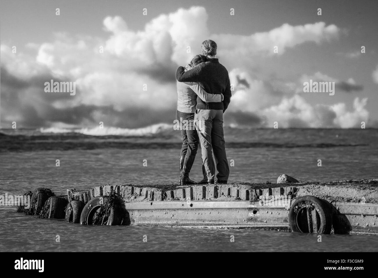 Couple hugging on jetty at Flamborough Head, Yorkshire,  with nice clouds. Good picture for contemplating future - Stock Image