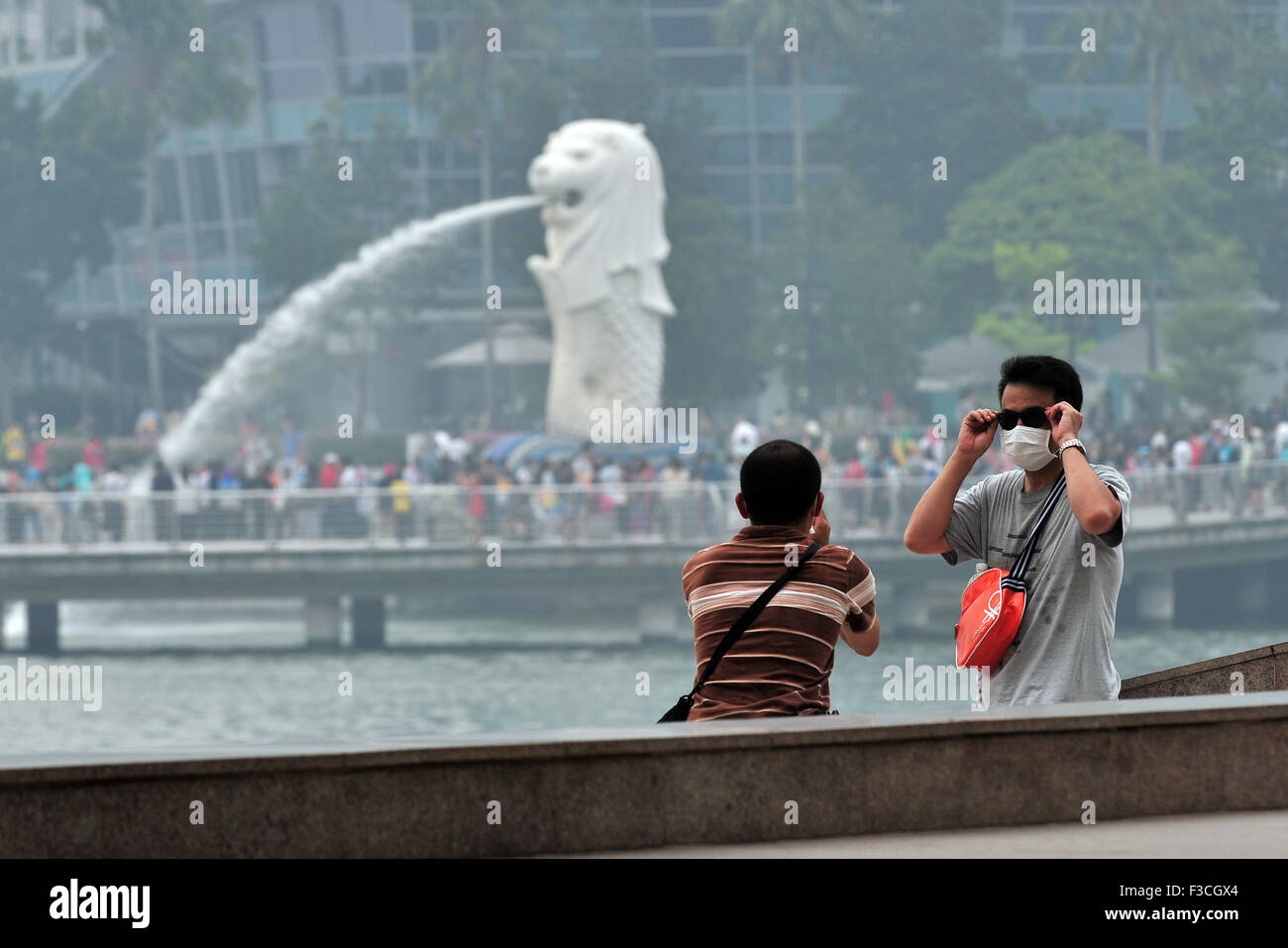 Singapore. 5th Oct, 2015. Tourists wearing masks take photos at Singapore's Marina Bay area on Oct. 5, 2015. - Stock Image