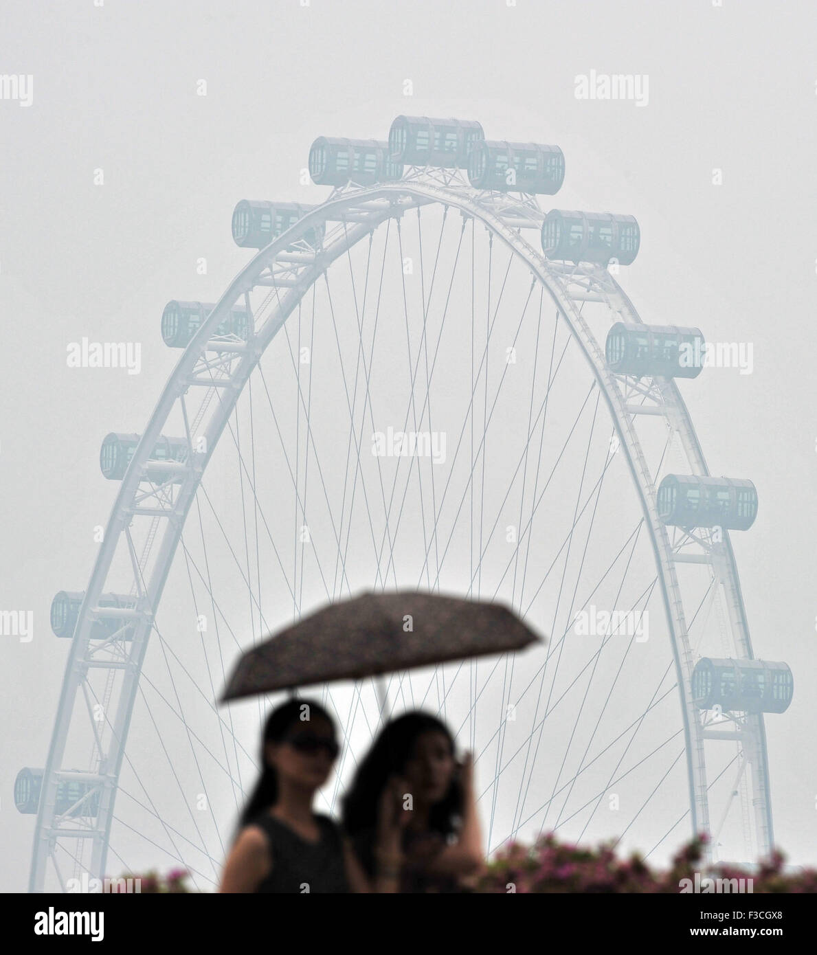 Singapore. 5th Oct, 2015. Pedestrians wearing masks walk in Singapore's Marina Bay area on Oct. 5, 2015. The - Stock Image