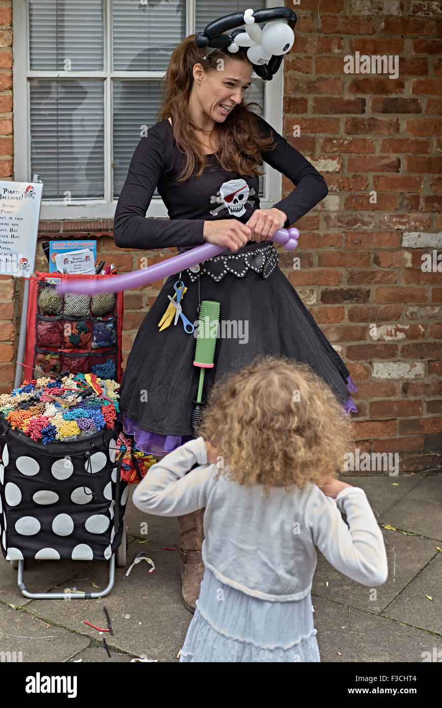 Female street entertainer shaping a balloon for an animated child. England UK - Stock Image