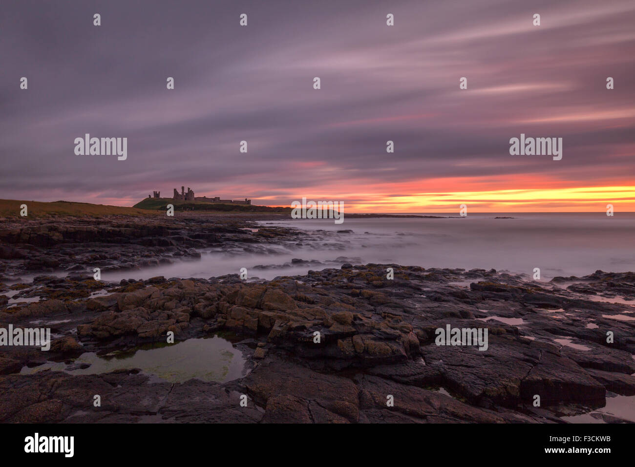 Dunstanburgh Castle at dawn, looking over the rocky shoreline, Northumberland, UK Stock Photo