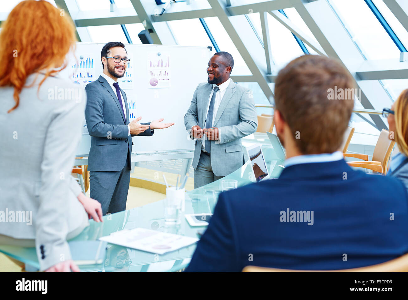 Asian businessman presenting colleagues their new business partner - Stock Image