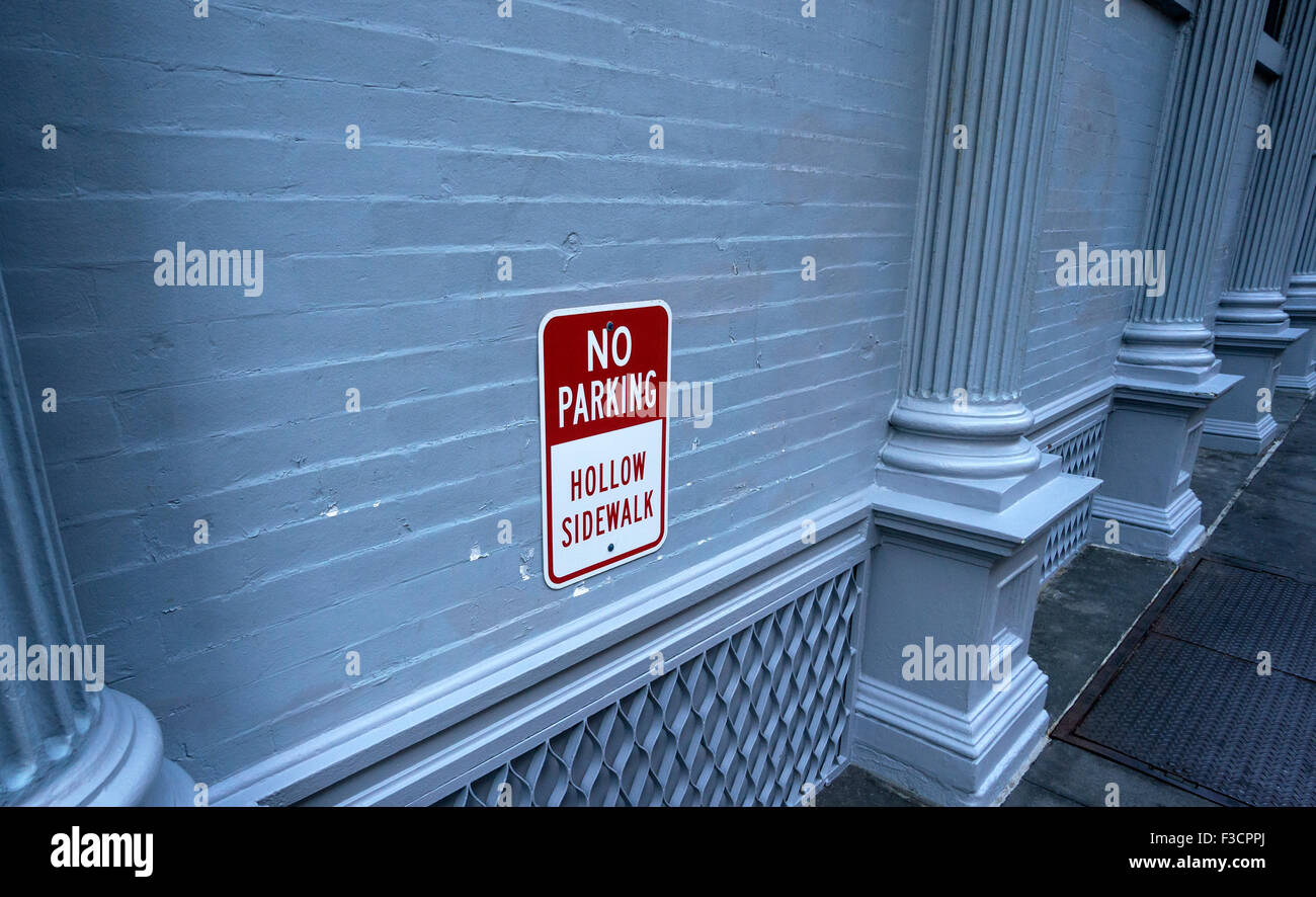 No Parking sign warns of a hollow sidewalk, which could cave in from the weight of a truck or car - Stock Image