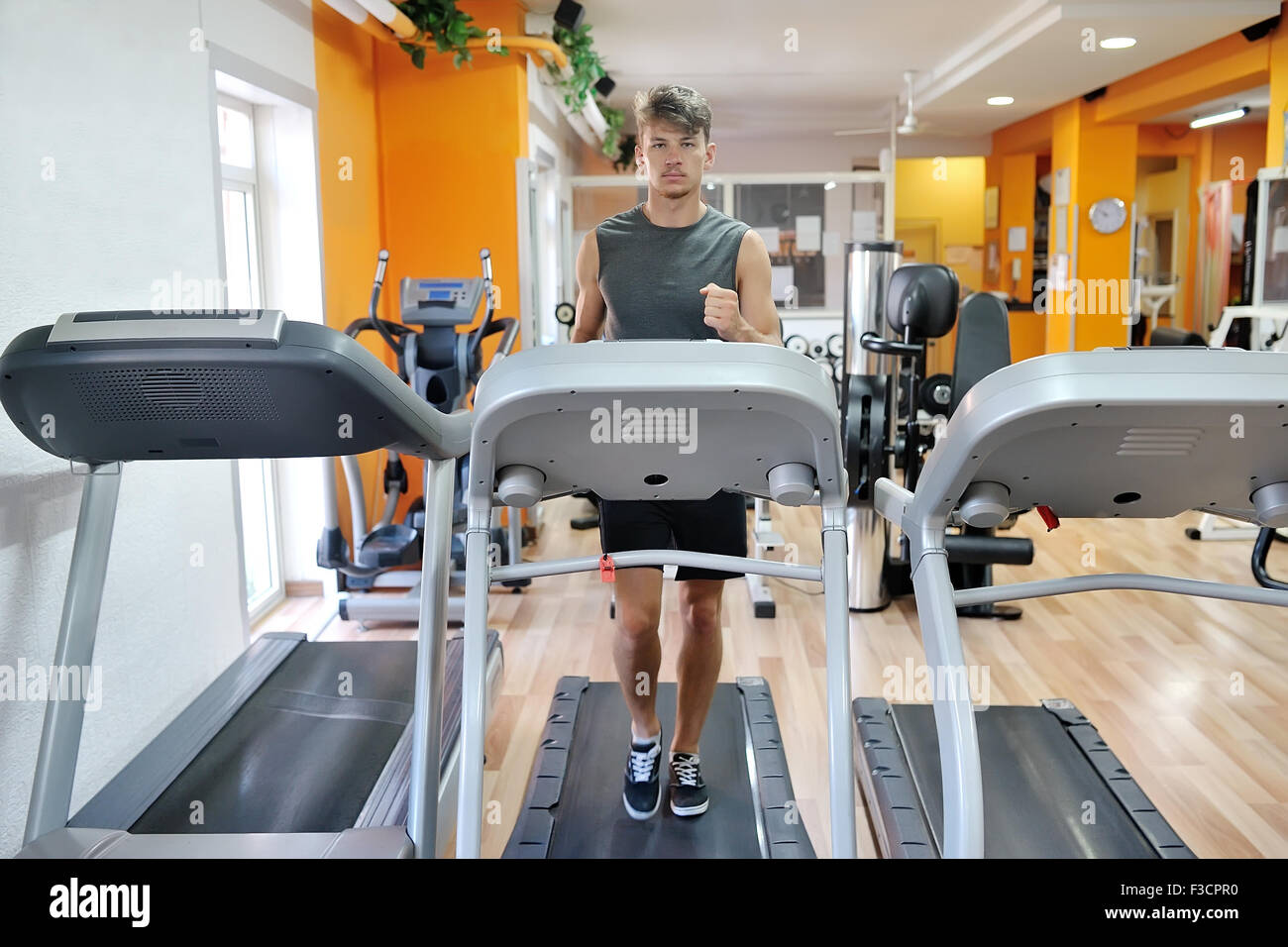 Young Handsome Athlete Running On Tapis Roulant In The Gym
