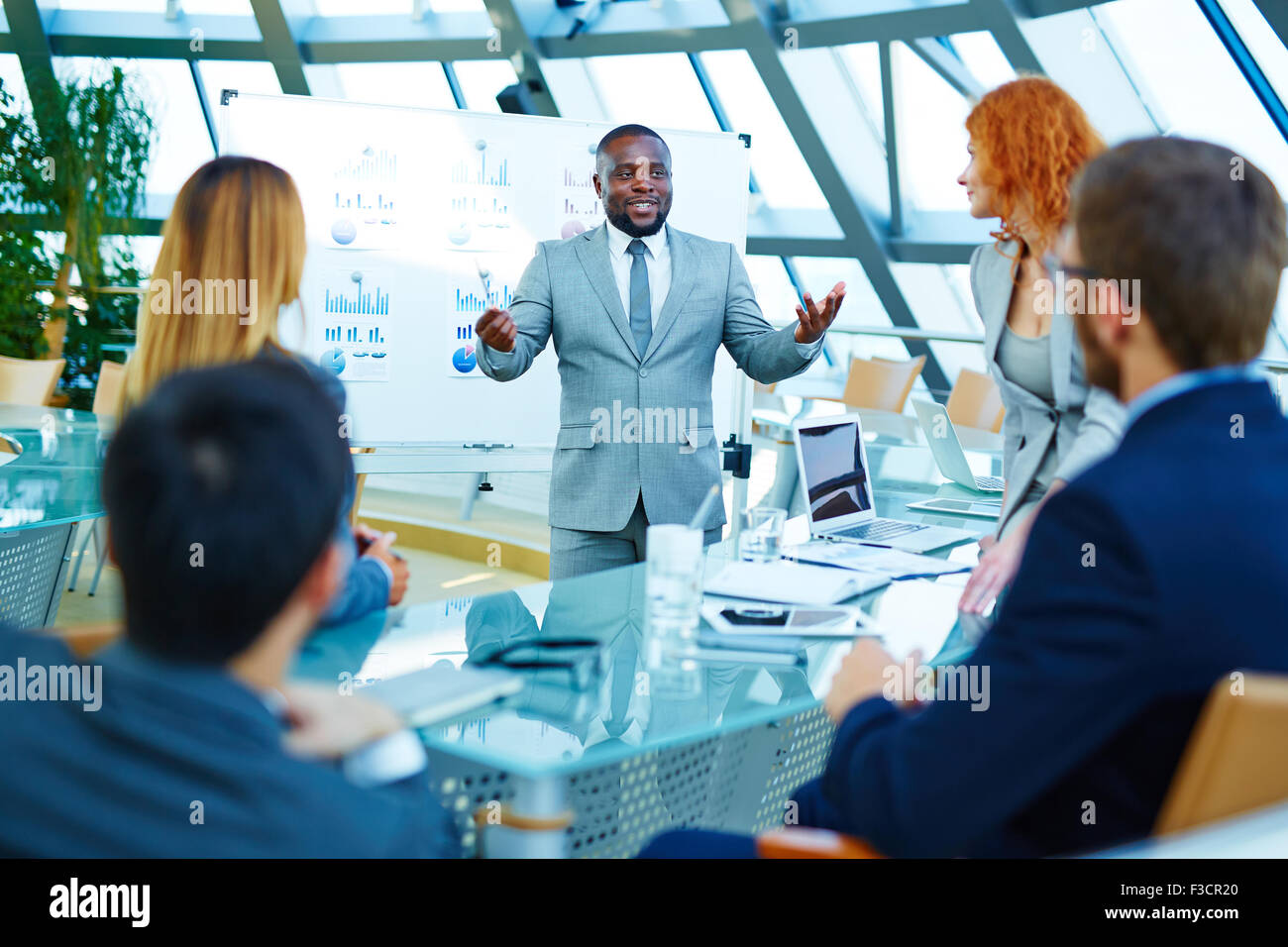 African-american businessman standing by whiteboard and voicing his opinion about data analysis to colleagues - Stock Image