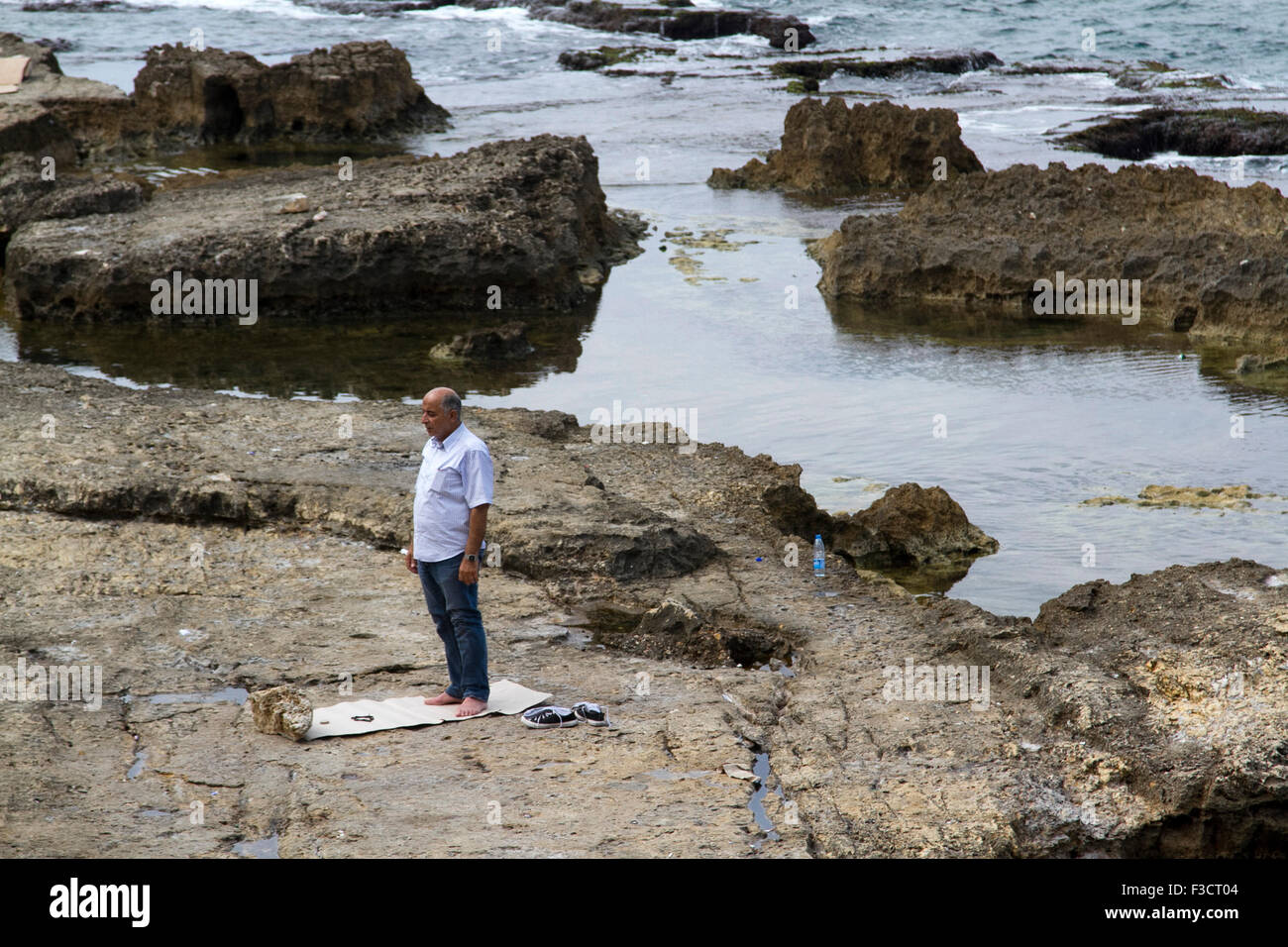 Beirut Lebanon 2015. Oct 2015. A man finds a spot on  the coastal rocks  off the Beirut shore to perform the  Islamic Stock Photo
