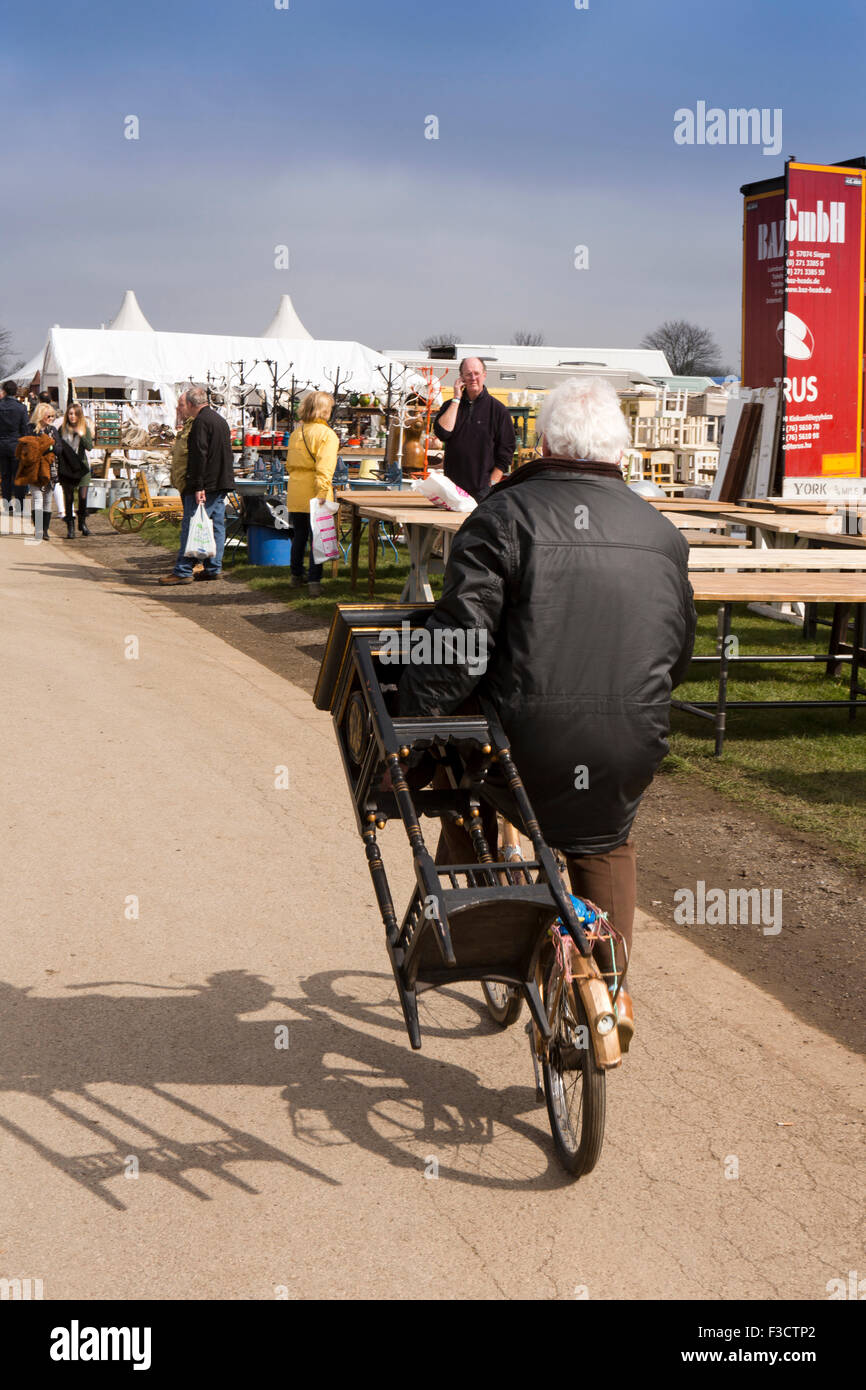 UK, England, Lincolnshire, Lincoln, Antiques Fair, man riding bicycle, whilst carrying small table - Stock Image