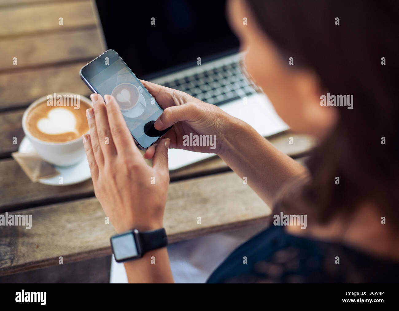 Close up shot of woman photographing a coffee of cup with her mobile phone while sitting at a cafe. - Stock Image
