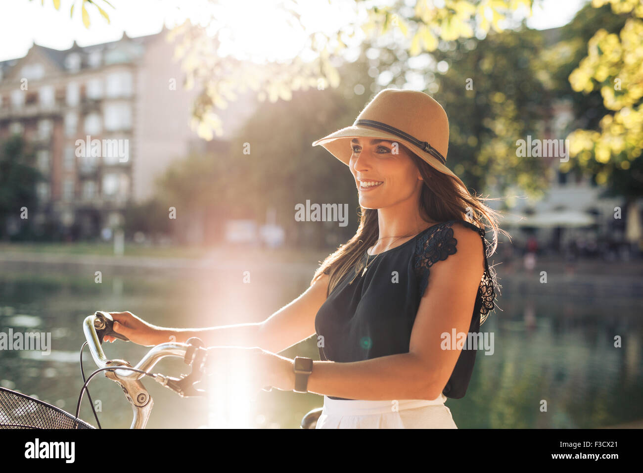 Portrait of happy young woman at the city park walking along a pond with her bicycle. European female model wearing - Stock Image