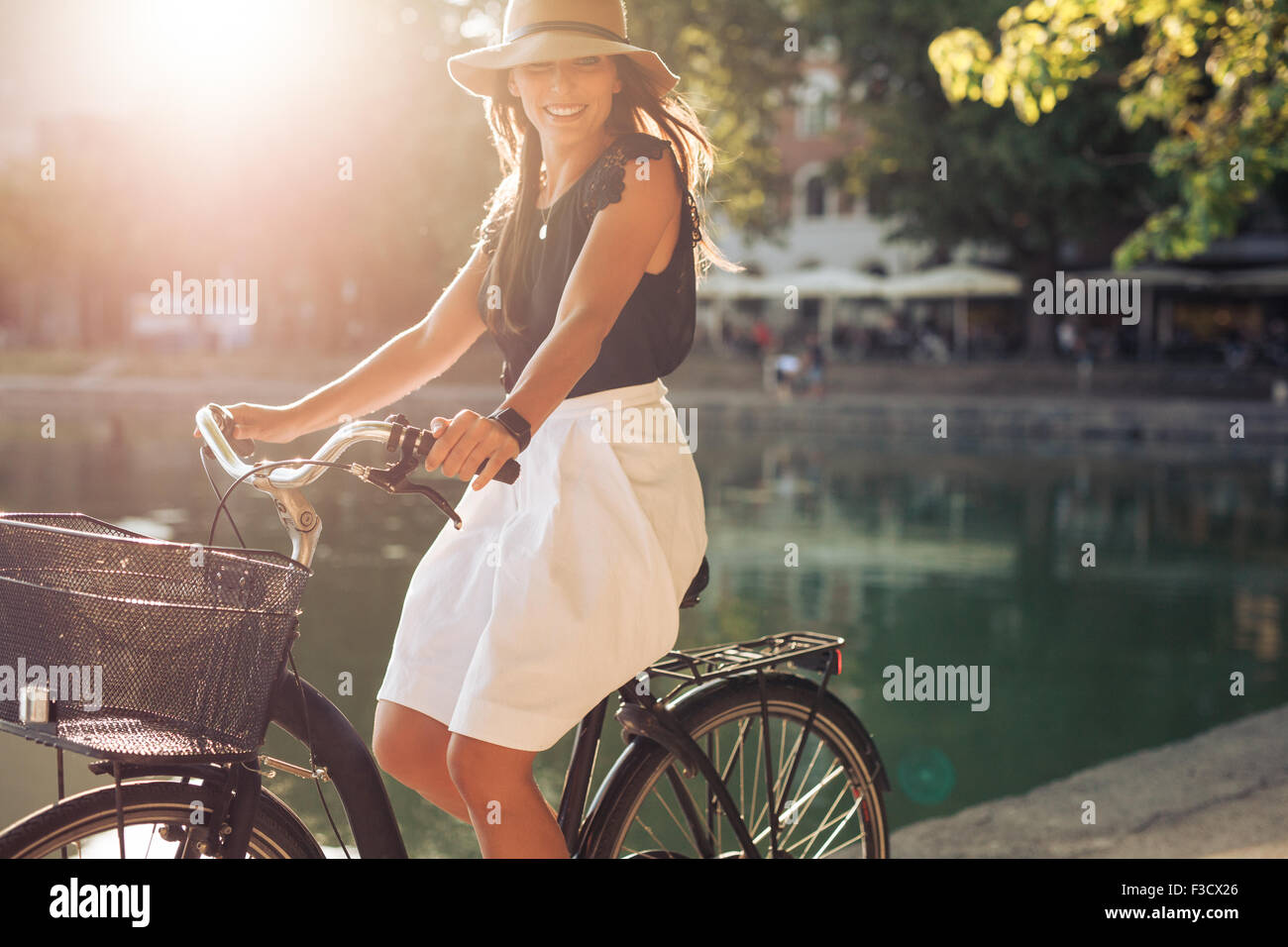 Portrait of happy young female cycling by a pond. Woman wearing a hat on a summer day riding her bicycle at city - Stock Image