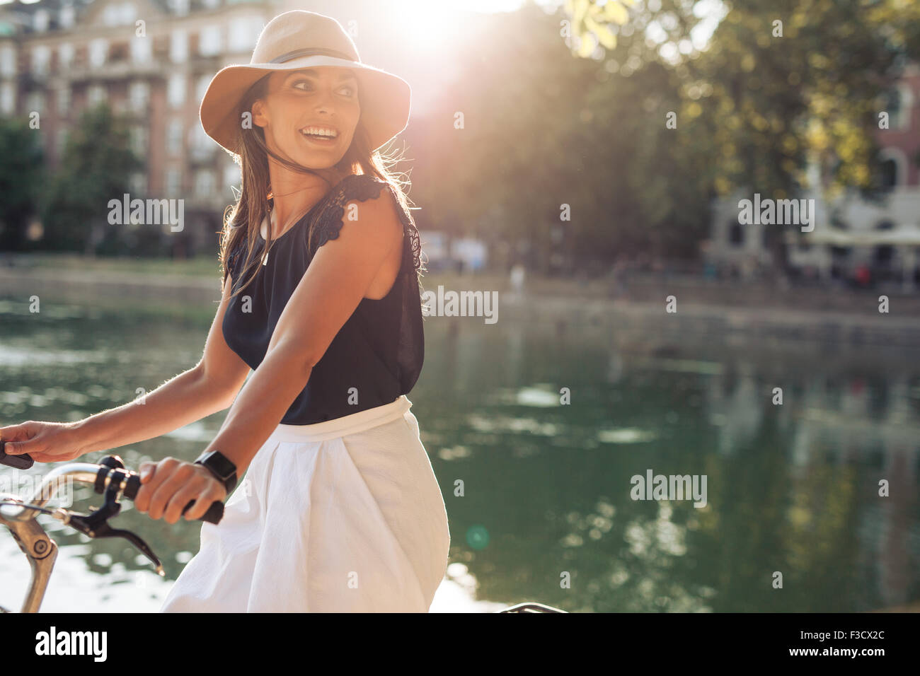 Portrait of happy young woman riding bicycle by a pond. Woman wearing a hat on a summer day looking over her shoulder. - Stock Image