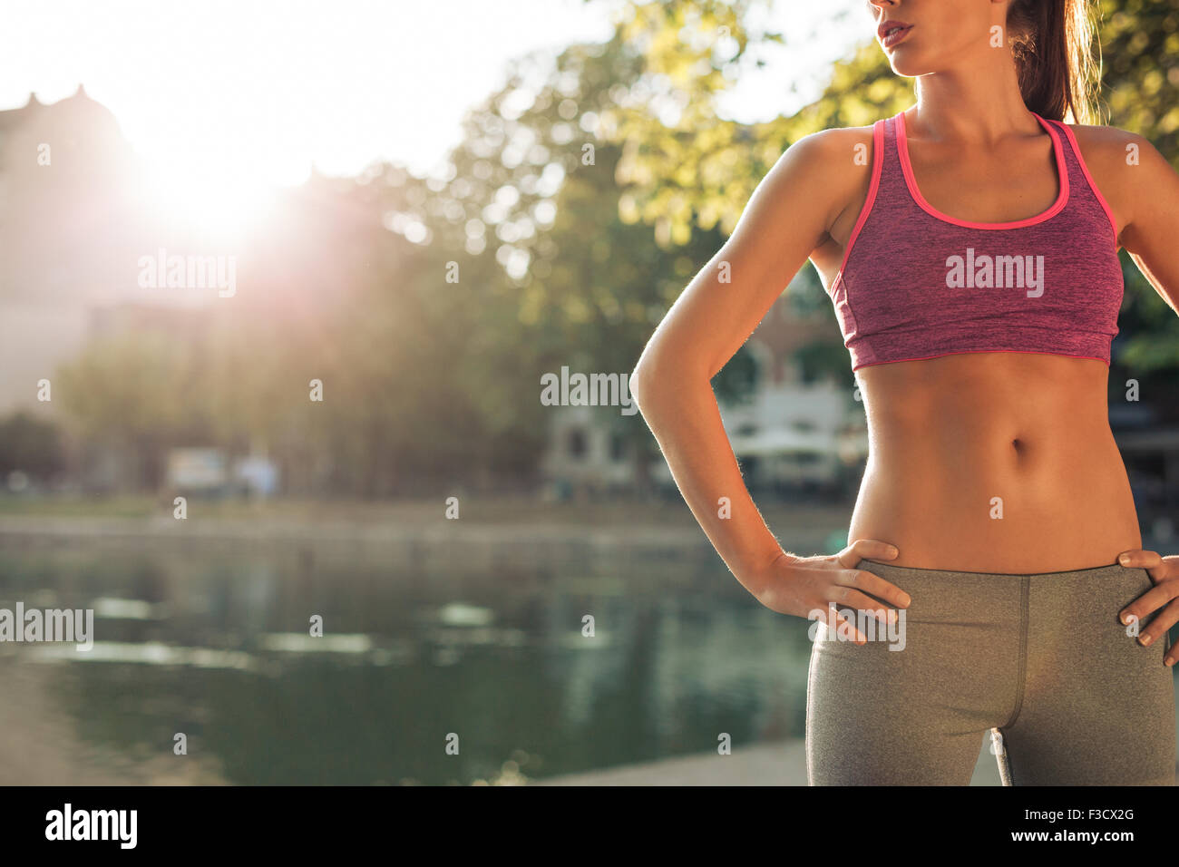 Cropped shot of fit young woman in sportswear standing with her hands on hips outdoors. Female runner ready for - Stock Image