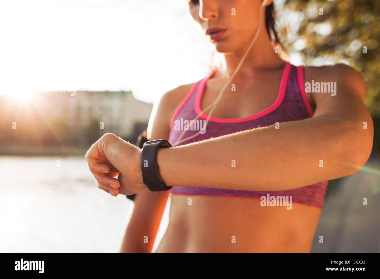 Young fitness woman looking at her smart watch while taking a break from outdoor workout. Sportwoman checking pulse - Stock Image