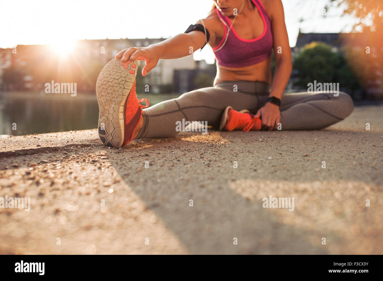 Cropped shot of female runner stretching legs before doing her summer workout. Woman warming up before outdoor workout - Stock Image