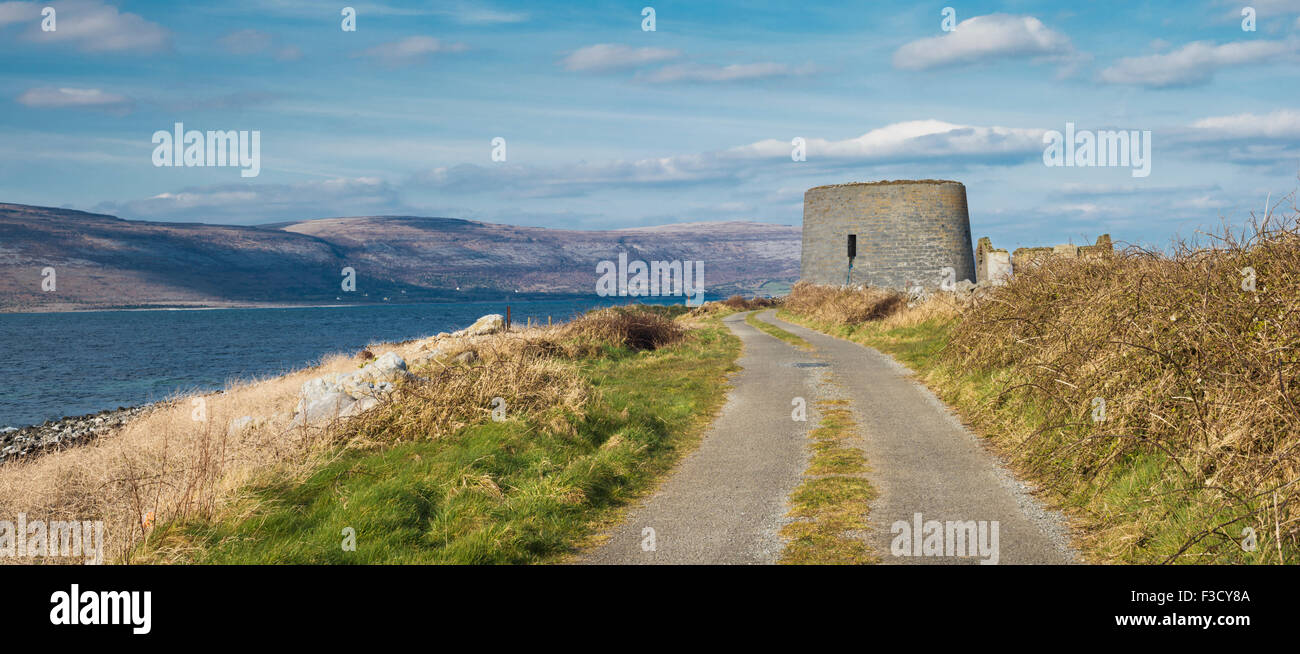 Track leading to the Martello tower at Finavarra Point, County Clare, with the Burren Mountains in the background - Stock Image