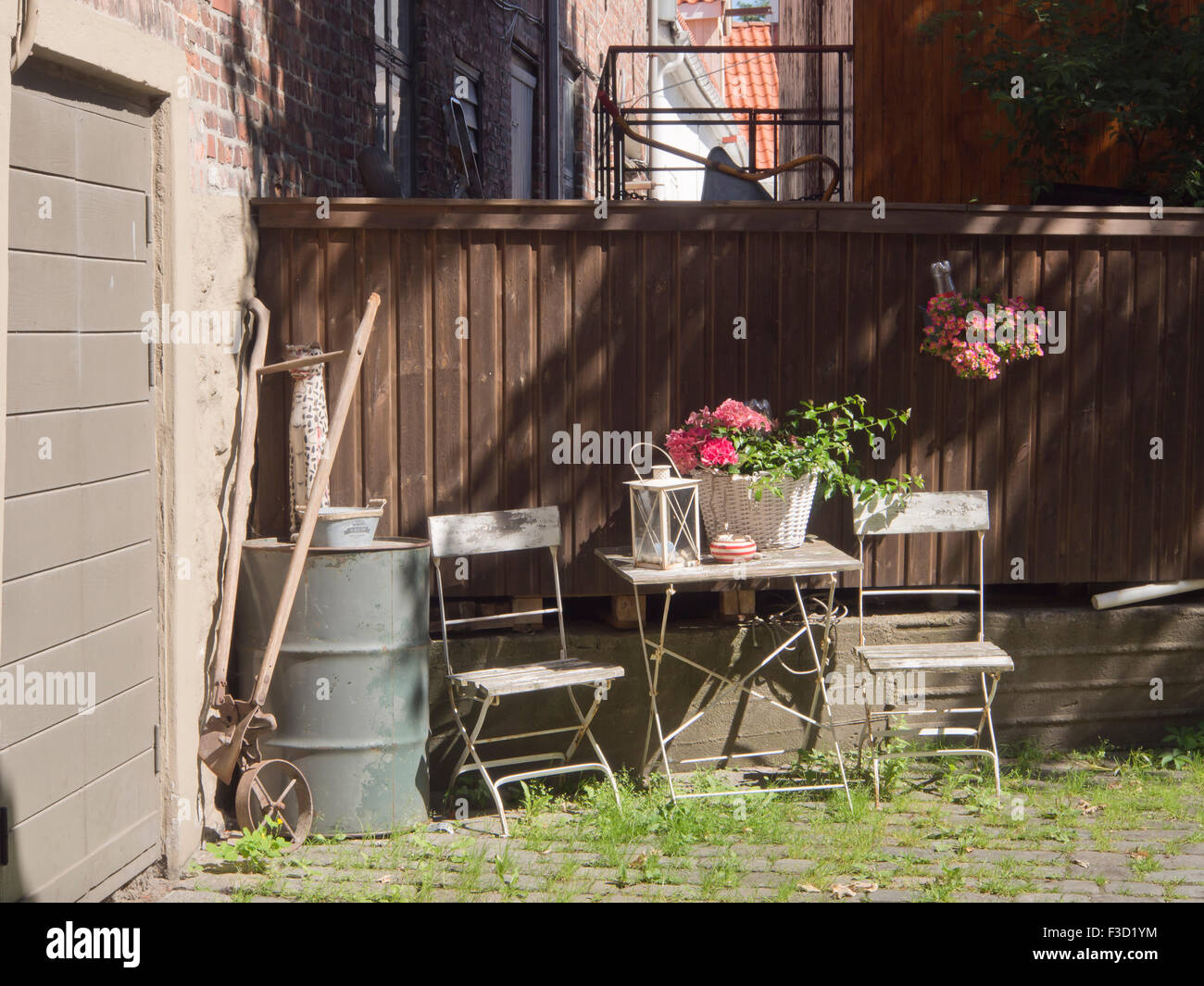 Sunny back yard with inviting table and chairs, encountered on a sightseeing in Gamlebyen Fredrikstad Norway - Stock Image